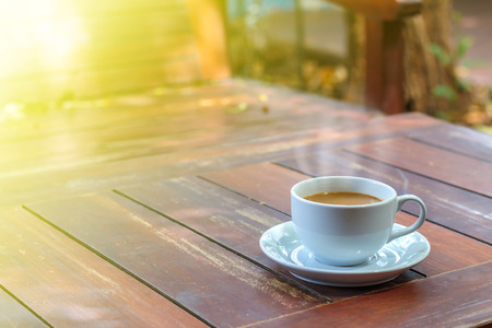Cup of hot coffee  on wood board in morning Standard-Bild