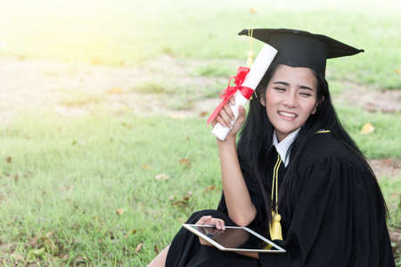 Happy graduate young Asian woman in cap and gown holding a certificated in hand