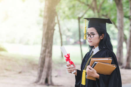 Happy graduate young Asian woman in cap and gown holding a certificated in hand, Education concept
