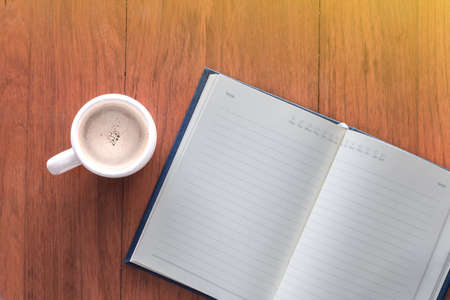 Note book with a cup of coffee on wood table Stock fotó