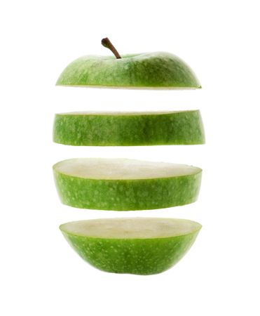 green apple cut into slices isolated over a white background