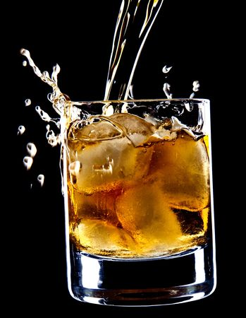 glass of whiskey and ice under the pouring whiskey isolated over black background photo