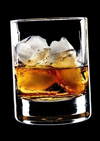 scotch: glas whisky en ijs geïsoleerde over zwarte achtergrond