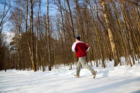 young man runs in the winter forest photo