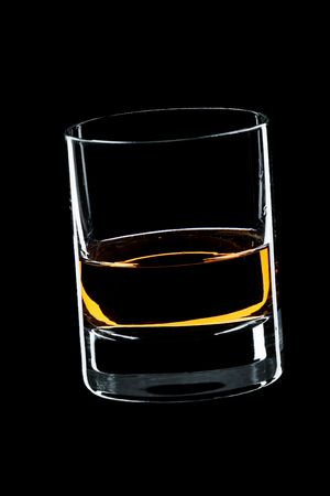 glass of whiskey isolated over black background photo