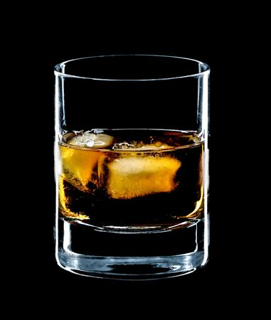hard liquor: glass of whiskey and ice isolated over a black background
