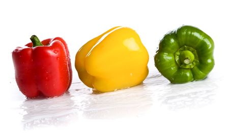 three fresh peppers under pouring water isolated over a white background photo