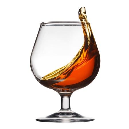 Splash of cognac in glass on white background