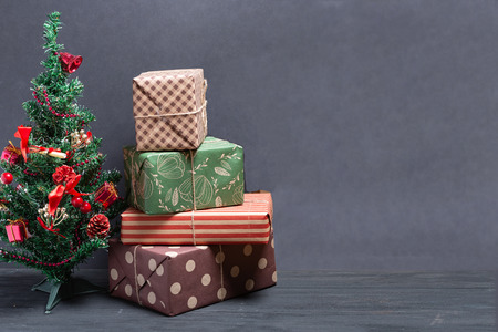 Varied and bright gifts under the Christmas tree on a black background Stock Photo