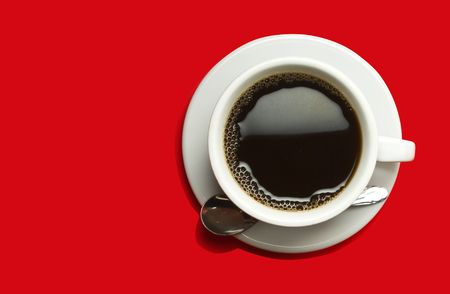 Picture of black coffee in a white cup on a red background photo