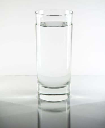 Glass of water on a reflective table top photo