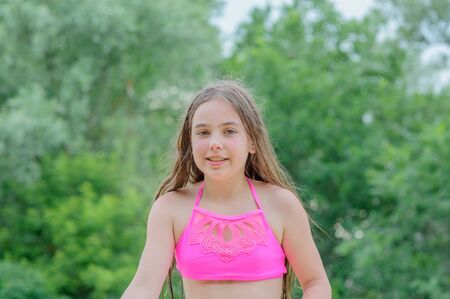 little brunette girl in pink bathing suit sitting in the sand. Little girl in a bathing suit by the river. Summer outdoor recreation by the river. Relax. girl 9 years old resting in the summer.