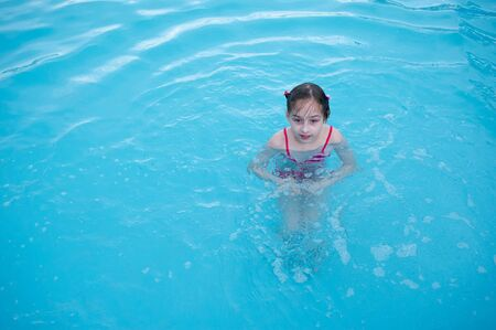 A little girl is resting in the summer in the aqua park. baby swims in the pool. Girl 9 years old resting by the water. Summer fun for children. Summer holidays for girls. 4th grade school.