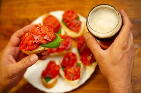 Hearty snack with different kinds of spreads on farmhouse bread served with a fresh yeast wheat beer on an old wooden table. Bruschetta with salmon, tomato, cheese, basil. Beer with foam.