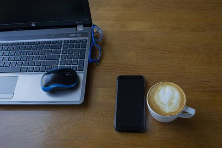 Workspace with laptop, a cup of coffee and a mouse for a laptop, phone, glasses on a white wooden table. Gray laptop, blue mouse for working at a computer, blue glasses for vision, cappuccino.