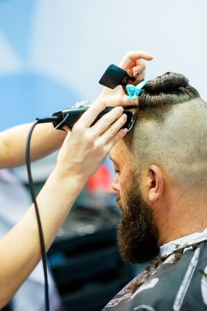 Hipster client visiting barber shop. Mens fashion. Bearded man after barber shop. Man hipster having barber shave barbershop hair machine. fashionable haircut, rear view. Work in a beauty salon. 免版税图像