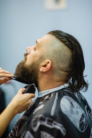 Hipster client visiting barber shop. Mens fashion. Bearded man after barber shop. Man hipster having barber shave barbershop hair machine. fashionable haircut, rear view. Weave braids.