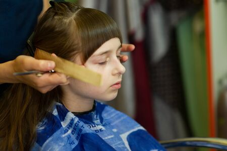 Hairdresser making a hair style to cute little girl. The girl cuts off the bangs. Work hairdresser. Change the image. Change hairstyle. Fashionable baby. A series of photos of haircuts baby bangs. 版權商用圖片