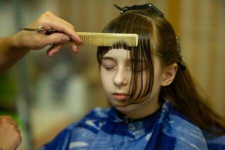 Hairdresser making a hair style to cute little girl. The girl cuts off the bangs. Work hairdresser. Change the image. Change hairstyle. Fashionable baby. A series of photos of haircuts baby bangs. 写真素材