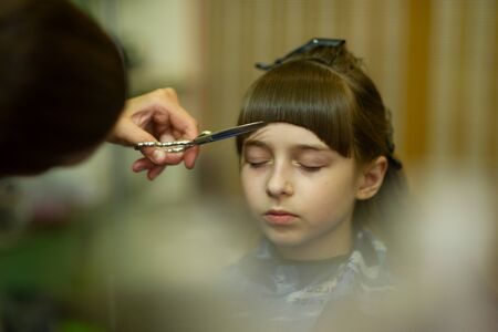 Hairdresser making a hair style to cute little girl. The girl cuts off the bangs. Work hairdresser. Change the image. Change hairstyle. Fashionable baby. A series of photos of haircuts baby bangs.