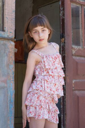 Adorable happy little girl outdoors. Portrait of caucasian kid enjoy summer. A girl of 9 years old in a dress in a flower. Beautiful haircut with bangs from the girl. Long hair of light brown color.