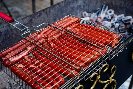 Grilling sausages on barbecue grill. Selective focus. Delicious street food. Food in nature. Grilled sausages. Meat dish on the fire, on the grill. Cooking grate. Many sosik in the cooking process Stock Photo