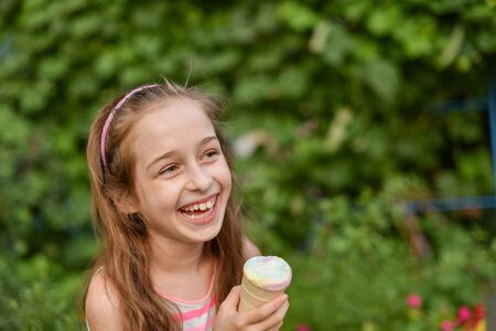 A little girl of 9 years old in a bright striped dress is eating a bright ice cream at an outdoor in a colorful striped bright dress. Sunny summer hot weather. The little blonde laughs wholeheartedly.