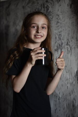 Little girl holding a coffee cup in black t-shirt. Mock up, perfect for putting your design on. Beautiful girl with long blond hair 9 years old drinks a drink from a black cup. A cute baby. teens