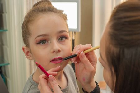 a little girl doing makeup before performing on stage. Preparation before the performance in the dressing room. Makeup artist makes the child makeup in the beauty salon. Hair stylist does her hair. Stock Photo