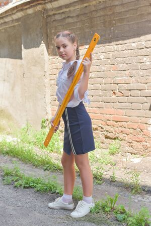 Elementary schoolgirl standing by school gate. Beautiful brunette schoolgirl in school uniform with a yellow ruler. Girl 10 years old with two pigtails and stylish hair color. Life style. School.