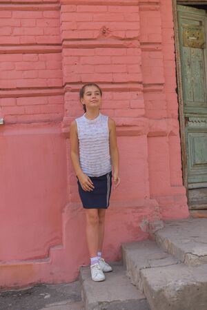 close up portrait of little beautiful stylish kid girl near red brick wall as background. White blouse, blue skirt - school clothes. Soon to school. Modern children. Two pigtails in a child. Beautiful