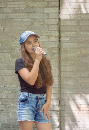 Beautiful little girl with microphone on brick wall background.The girl in denim shorts sings into a microphone on a city street. Beautiful brunette. Vote. Long hair in a child. Lifestyle