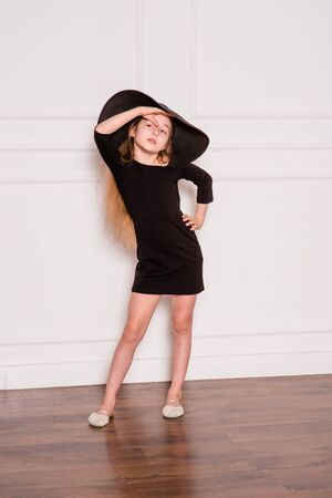 little fashion model in dress photo in photostudio backstage. A child of a girl of 8-9 years old is posing as an adult. Long hair. Modern children. Schoolgirl on a photo shoot.