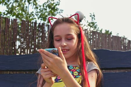 Little girl child, on the head a rim in the form of cat ears, portrait. Girl with fashionable red hair. Girl talking on the phone while sitting on a swing. Long blond hair and a girl. Modern children Stok Fotoğraf