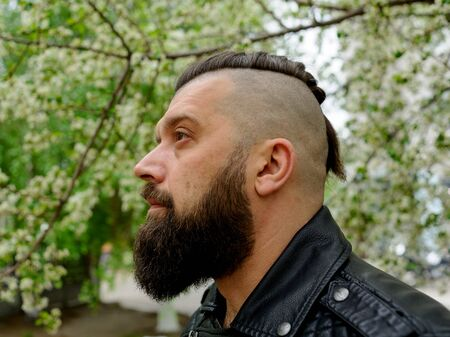 A man in a leather jacket with a brunette beard. brutal man brunette with beard on her face. street style in clothing: leather jacket. A man with a pigtail on his head and a fashionable haircut.