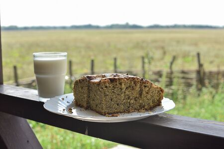Bun with poppy seeds with a glass of milk. Milk in a glass and poppy seed cake on a field background. Pie with a cup of milk in the village on the background of the field. Beautiful nature and food. Stok Fotoğraf