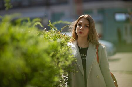 Stylish young pretty girl in a gray coat looks at the camera and smiles slightly against the background of the city. A girl stands by a green bush.Girl in a gray coat on a background of the city
