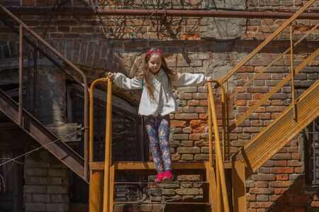 Tracking shot of little girl in linen dress lying on railing of staircase and sliding down.Little girl on a metal staircase.Little and beautiful girl in a purple hoop with cat ears and in a white coat