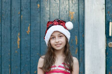 Little girl in santa claus hat on blue background.A little girl is having fun and playing in christmas eve at Santa Claus hat, in a bathing suit, a background of blue.concept of christmas and holidays