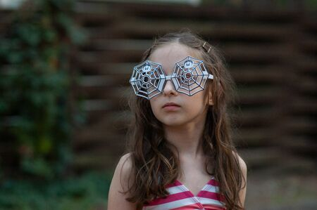 Little girls wearing glasses. Halloween concept.A girl of 9-10 years old wore glasses with a spider design for Halloween or a summer theme party. A girl in a swimsuit on vacation.
