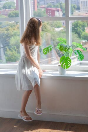 Little girl in white dress.Little girl in a white dress by the window.Little girl at the window with a city view.Pensive girl. Brown hair at the girl.Lace white dress for a girl of 9-10 years old Stockfoto