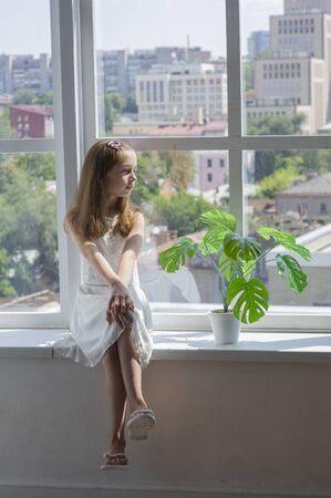 Little girl in white dress.Little girl in a white dress by the window.Little girl at the window with a city view.Pensive girl. Brown hair at the girl.Lace white dress for a girl of 9-10 years old