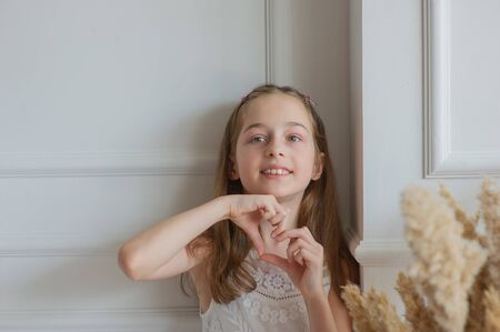 Beautiful little girl shows with gestures I love you.A girl shows love.Cute girl in a white dress shows a heart with hands.Portrait of a little girl in the Studio with a white background.Little girl Stok Fotoğraf