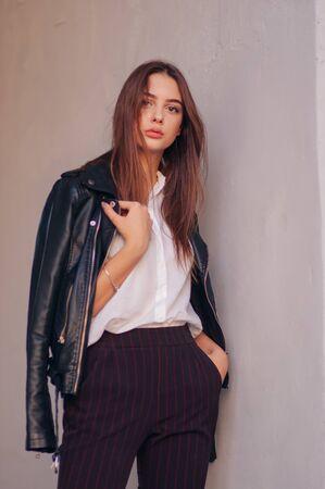 jeune fille dans une veste en cuir noire se dresse sur le fond d'une rue de la ville. Fille dans une veste en cuir sur fond gris. Une série de photos avec une belle brune en extérieur en ville. Banque d'images