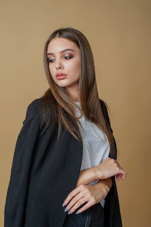 Girl with professional make-up. A girl in a black jacket and white t-shirt poses like a stylish lady on a beige background. Girl with long hair and beautiful eyes. Casual woman. Business lady 版權商用圖片
