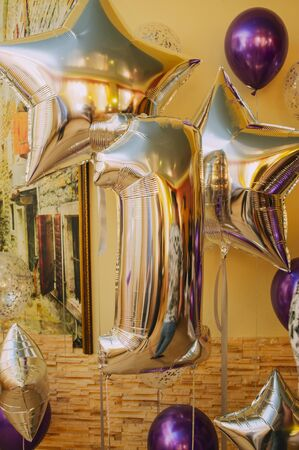 Decoration for 1 years birthday, anniversary. Balloon number one. The digit is a unit of gold color. Balloons in gold and purple. Celebration of the holiday. Ball star platinum or gold color. Stock fotó