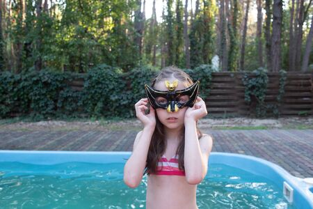 Halloween concept.Black Bat Points.Little girl in a bat mask.A girl of 9-10 years old on Halloween or a summer theme party.teenager, nature.bat, mask, glasses carnival, carnival mask, black mask.