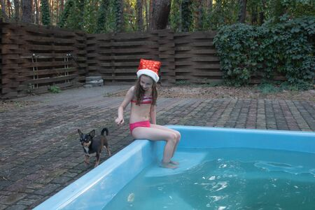 A child is playing with a santa claus hat. Happy little girl in Santa Claus hat outdoors in summer.Concept New Year or Christmas series of photos.Little girl in a Santa Claus hat by the pool Stock Photo