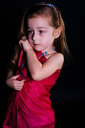 Beautiful little girl child.Little girl posing in studio with a cloth on a black background. A child with brown hair poses in a pink cape in the studio as an adult. The child imagines himself an adult