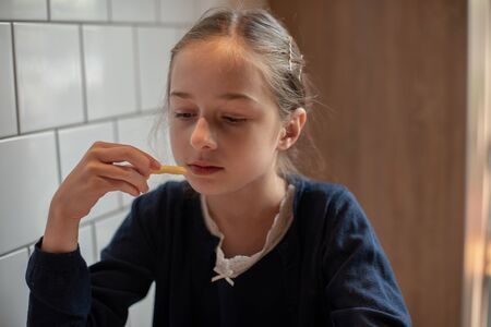 Happy teen girl eating a burger and french fries. Schoolgirl eating a burger.A girl of 9 years old has lunch after attending school with a burger.The child enjoys lunch. Schoolgirl in a school uniform